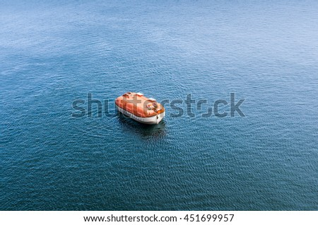 Lifeboat of enclosed and rigid type awaiting rescue during exercises of cruise ship crew. Emergency safety training and marine evacuation drills are performed regularly by every cruise ship crew. - stock photo