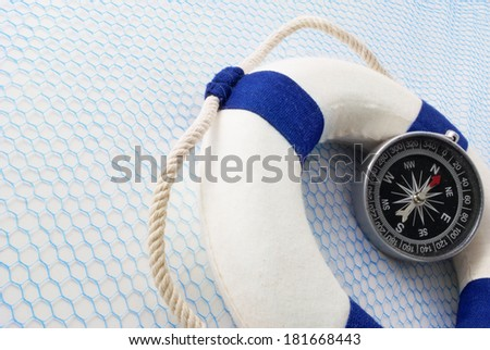 Lifebuoy and compass on a blue grid over white background. - stock photo