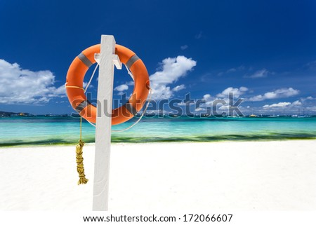 Lifebuoy ring on tropical beach - stock photo