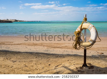 Lifebuoy ring on tropical beach. Rescuer buoy on the sand beach for your concept of the summer trip in a sea lagoon. - stock photo