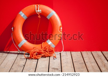 Lifebuoy stands on wooden floor of lifeguard station - stock photo