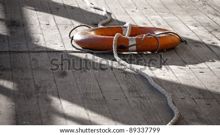 Lifebuoy with rope on the naval deck - stock photo