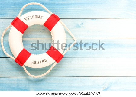 Lifebuoy with Welcome aboard phrase on wooden background - stock photo