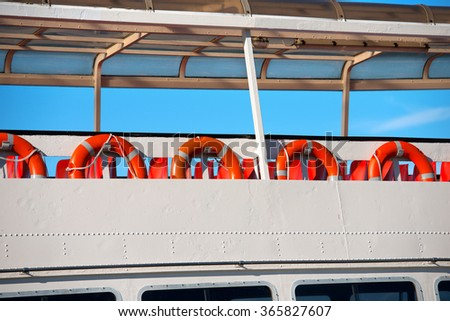 Lifebuoys in a Ferry Boat / A row of red and orange life buoys on the deck of a passenger ship - stock photo