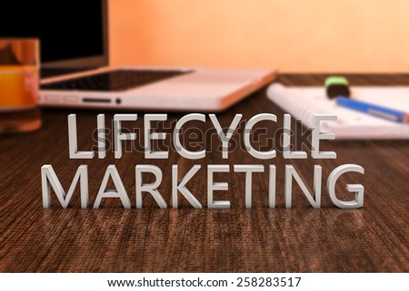 Lifecycle Marketing - letters on wooden desk with laptop computer and a notebook. 3d render illustration. - stock photo