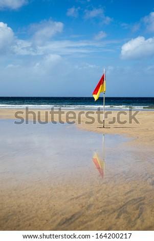 Lifeguard flag on a Cornish beach - stock photo