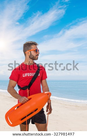 lifeguard on duty keeping a buoy at the beach - stock photo