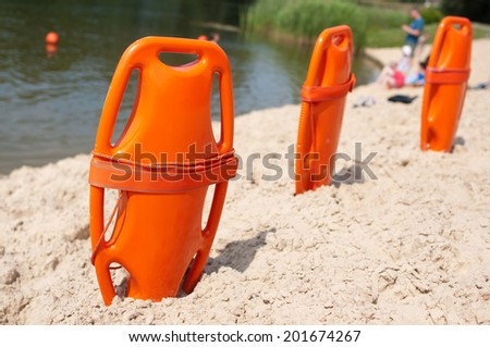 Lifeguard orange rescue equipment on beach in the summer - stock photo