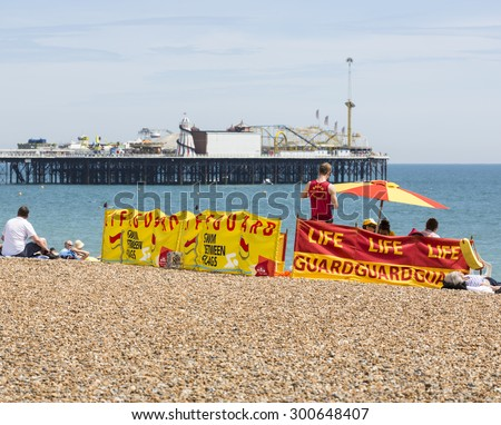 Lifeguard station on the beach in Brighton, East Sussex, UK with Palace Pier (Brighton Pier) behind, on a summer day - stock photo