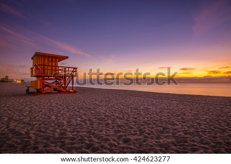 Lifeguard tower in a typical colorful Art Deco style at sunshine, with purple sky and Atlantic Ocean in the background. World famous travel location. Miami beach, Florida.  - stock photo