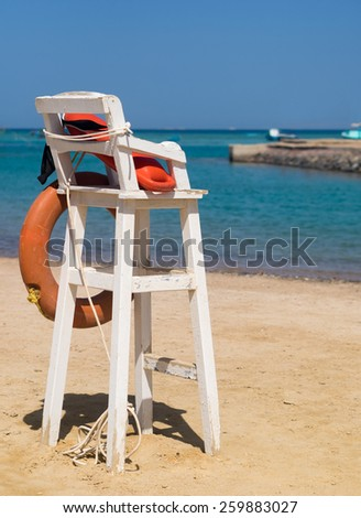 Lifeguard tower on a sand beach. Lifeguard station with lifebuoy on a coast of a tropical resort. Lifesaver service on summer beach. - stock photo