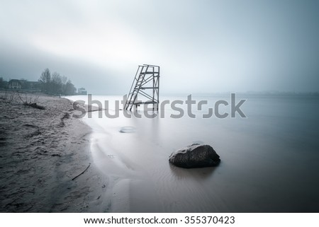Lifeguard tower on the late autumn beach. Big stone in the water on foreground. Long exposure shot. - stock photo