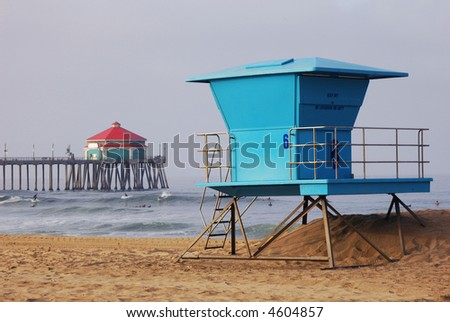 Lifeguard Tower with pier and surfers in distance, Huntington Beach, CA - stock photo
