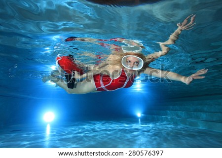 Lifeguard with red swimsuit, diving mask and safety buoy underwater in the pool  - stock photo