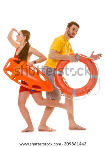 Lifeguards running with rescue tube and ring buoy on duty. Man and woman supervising swimming pool. Accident prevention. - stock photo