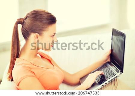 lifestyle and internet concept - woman using laptop at home - stock photo