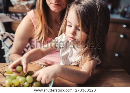 lifestyle capture of pregnant woman with daughter on the kitchen eating grapes - stock photo