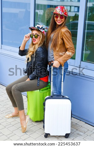 Lifestyle fashion portrait of two best friend posing near airport before they travel, holding their bright luggage, having fun, wearing bright hipster clothes hats and sunglasses. - stock photo