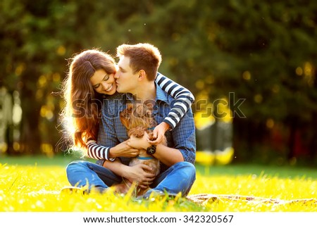 Lifestyle, happy family of two resting at a picnic in the park with a dog - stock photo