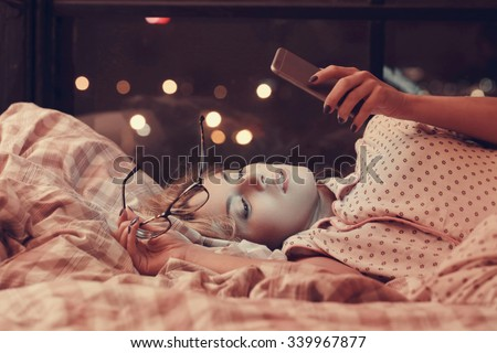 Lifestyle, home. Girl lying in bed - stock photo
