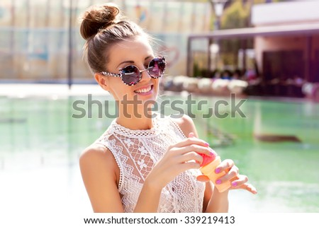 lifestyle image of Crazy funny pretty woman posing at the street, wearing trendy summer outfit ,cool flower round sunglasses,cool bubble party. Holding big pink lollypop,Enjoy music festival.  - stock photo