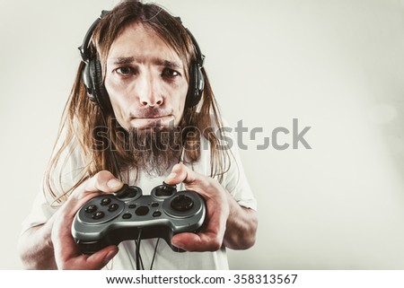 Lifestyle of young people. Student man spending time on playing games video games console playstation. Long haired guy focus on gaming. - stock photo