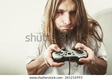 Lifestyle of young people. Student man spending time on playing games videogames console playstation. Long haired guy focus on gaming. - stock photo