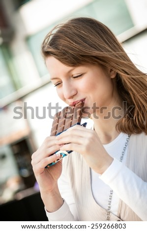 Lifestyle outdoor scene - young beautiful woman eating chocolate - stock photo