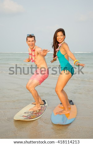 Lifestyle outdoors portrait of happy couple standing on surfboard on the beach. Ready to surfing. Wearing stylish blue bikini, pink shorts. Young interracial couple in love, Asian woman, Caucasian man - stock photo