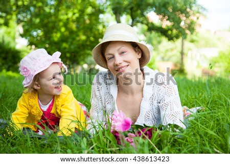 Lifestyle portrait mom and daughter on the grass - stock photo