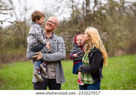 Lifestyle portrait of a family of four including a mother, father, son, and daughter interacting showing happiness. - stock photo