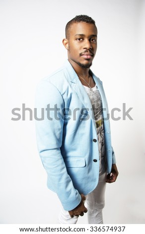 Lifestyle portrait of a handsome young guy with fit body, wearing stylish blue jacket and white trousers. Bright colors. Positive emotions - stock photo
