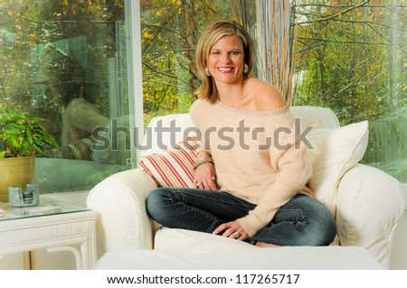 Lifestyle Portrait of a Pretty Blonde Sitting in a Sun Room Setting - stock photo