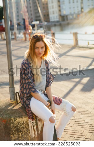 Lifestyle portrait of a young attractive woman sitting outdoors with a skateboard - stock photo