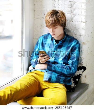 Lifestyle portrait of a young man texting sms - stock photo