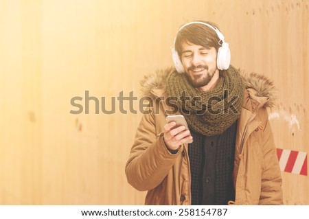 Lifestyle portrait of a young man using a smart phone outdoors instagram tones applied - stock photo