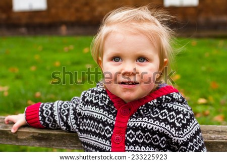 Lifestyle portrait of a young one year old child outdoors. - stock photo