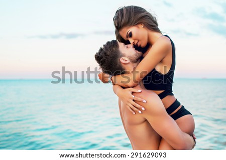 Lifestyle portrait of  attractive young woman and her handsome boyfriend keeps on  hands .  Beautiful couple  having fun sea background . Warm  evening colors. - stock photo