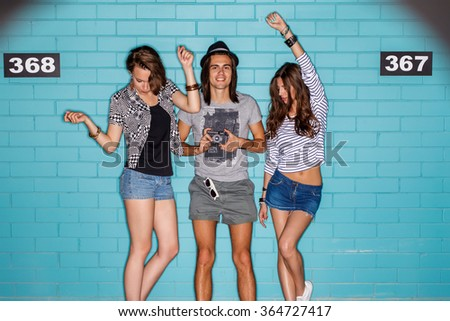 Lifestyle portrait of beautiful best friend hipsters posing for the camera in front of brick wall enjoying day off and have fun. Two beautiful dancing girls and smiling boy in hat with photo camera. - stock photo