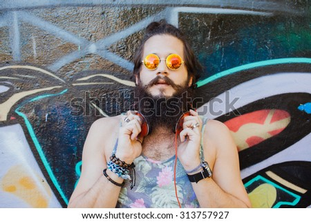 lifestyle portrait of teen man outdoors portrait,car trip.Happy and active.mans hairstyle.trendy man sunglasses,sport style,young dj,t-shirt and shorts,Cool man with beard.big earphones,success  - stock photo