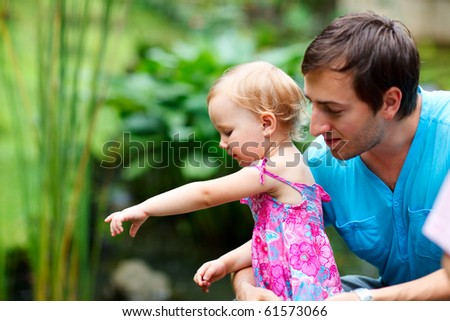 Lifestyle portrait of young father and his little daughter outdoors - stock photo