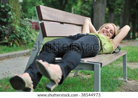 Lifestyle shot of young beautiful smiling woman lying on bench in park outside - stock photo