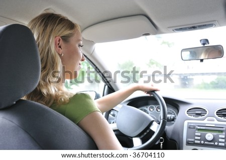 Lifestyle shot of young cheerful woman driving car - rear view - stock photo