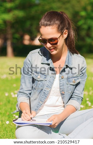 lifestyle, summer vacation, education and people concept - smiling young girl writing with pencil to notebook and sitting on grass in park - stock photo