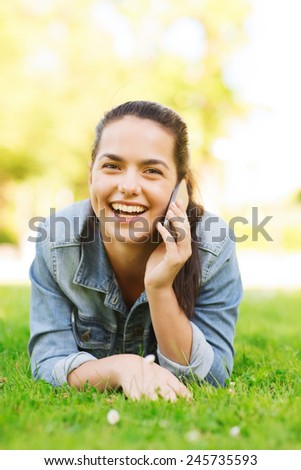 lifestyle, summer vacation, technology, leisure and people concept - laughing young girl with smartphone talking and lying on grass in park - stock photo