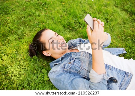 lifestyle, summer vacation, technology, leisure and people concept - smiling young girl with smartphone lying on grass in park - stock photo