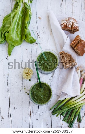 Lifestyle with green smoothies on a glass, swiss chard, bunch of garlic with  whole bread, taken on vintage white surface. Fresh and vegetarian drink concept. Rustic style. Top view.   - stock photo