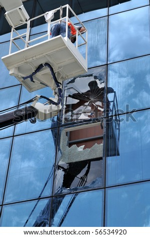 Lift operator changing the broken windows of an office - stock photo