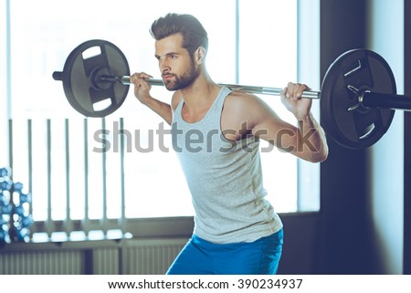 Lifting weight. Young handsome man in sportswear lifting barbell at gym - stock photo