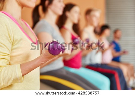 Lifting weights in a pilates class at fitness studio - stock photo